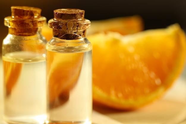 Óleo essencial de laranja. óleo de laranja em uma garrafa de vidro e fatias de laranjas