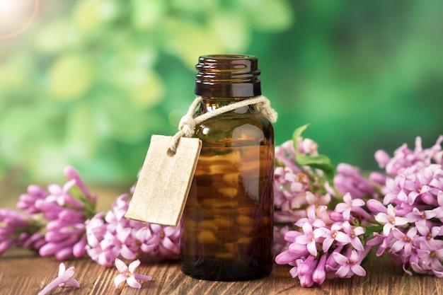 Óleo essencial de lilás em um frasco de vidro em um de madeira, relaxamento, spa.