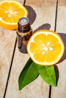 Óleo essencial de limão em uma pequena garrafa. foco seletivo.