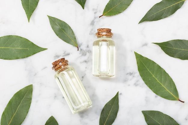Óleo essencial de louro na mesa de mármore. baía de óleo na garrafa de vidro com conta-gotas. laurus nobilis