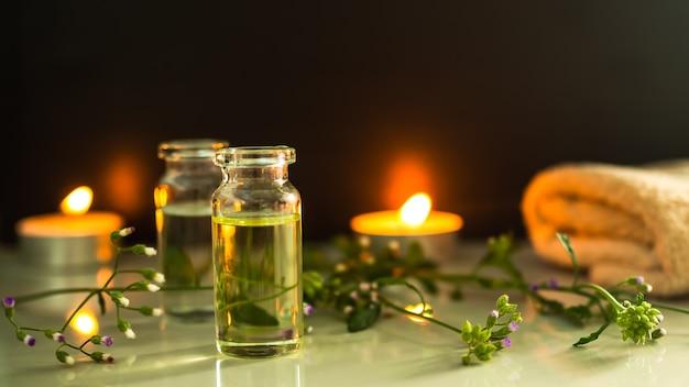 Óleo essencial de massagem com vela e pedrinha em fundo preto