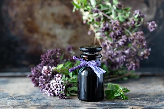 Óleo essencial de orégano em frasco de vidro na mesa de madeira. copie o espaço