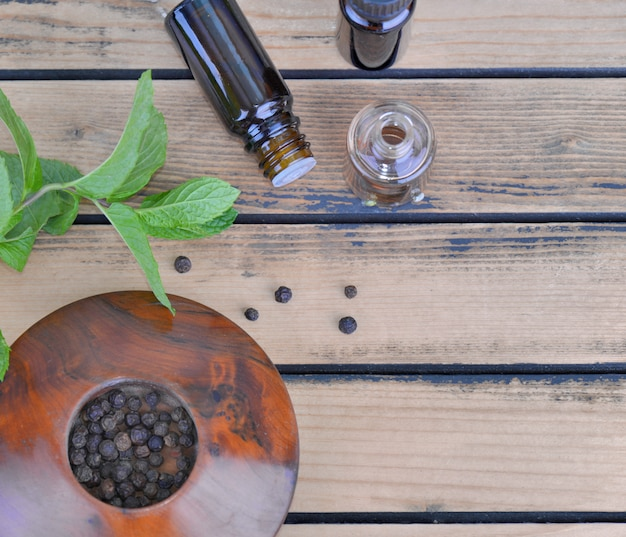 Óleo essencial de pimenta de hortelã-pimenta e eaf fresco de hortelã com sementes de pimenta na tigela sobre fundo de madeira