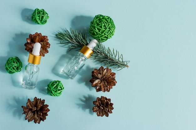 Óleo essencial de pinho e abeto em pequenos frascos conta-gotas de vidro sobre fundo azul.