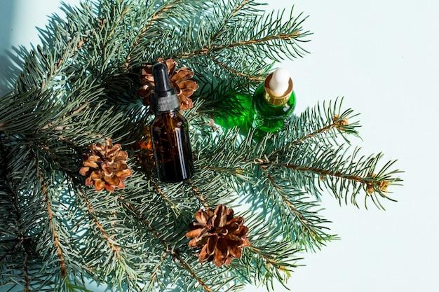 Óleo essencial de pinho e abeto em pequenos frascos conta-gotas de vidro sobre fundo azul. Foto Premium