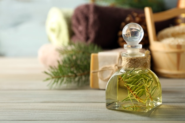Óleo essencial de pinho, sabonete artesanal e creme com extrato de pinho e tratamentos de spa em fundo de madeira