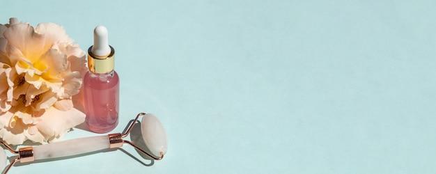 Óleo essencial de rosa cosmético e massageador facial com rolo de quartzo rosa pedra de gua-sha para massagem facial em casa. cuidados com a pele e conceito de tratamento de rosto. bandeira