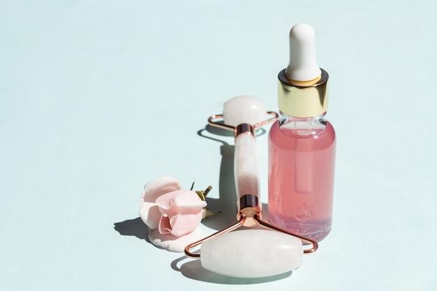 Óleo essencial de rosa cosmético e massageador facial de pedra gua-sha de rolo de quartzo rosa para massagem facial em casa. cuidados com a pele e conceito de tratamento de rosto.