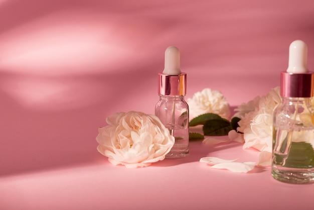 Óleo essencial de rosa em frasco cosmético perto de flores rosas frescas contra fundo rosa.