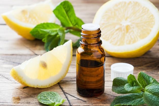 Óleo essencial do limão na garrafa, fatias da fruta fresca no fundo de madeira. fragrâncias naturais.