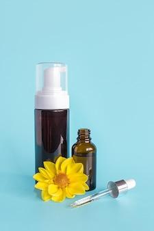 Óleo essencial em frasco conta-gotas pequeno aberto marrom com pipeta de vidro deitado, frasco grande com dispensador branco