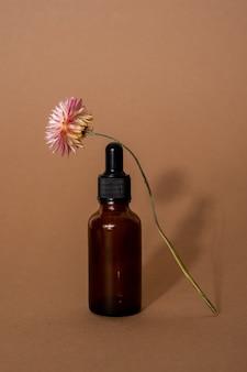 Óleo essencial em frasco de vidro marrom com pipeta e flor seca na superfície bege