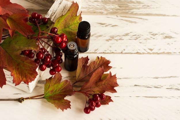 Óleo essencial natural de sementes de viburnum em garrafas de vidro em um fundo branco de madeira. um conceito natural de autocuidado.