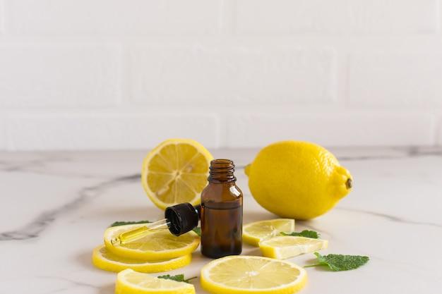 Óleo facial hidratante com extrato cítrico no contexto de rodelas de limão e fundo branco. o conceito de cuidados com o rosto e o corpo.