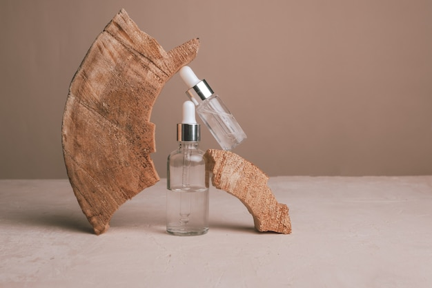 Óleo mineral ecológico em frascos de vidro com pipeta e madeira natural em fundo marrom