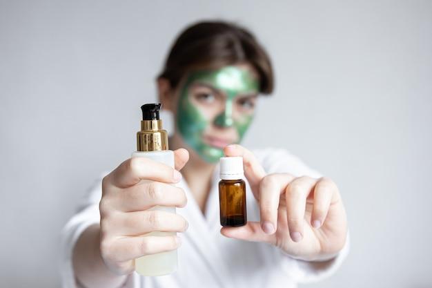 Óleo natural em uma jarra e um produto de beleza nas mãos de uma jovem mulher com produtos para o rosto