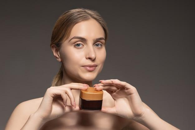 Óleo. retrato de jovem modelo feminino isolado na parede cinza. linda mulher caucasiana com pele saudável e bem cuidada. estilo e beleza, conceito de cuidados com a pele. fechar-se.