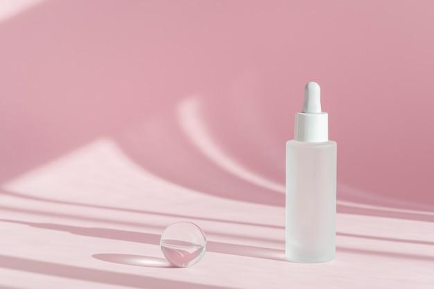 Óleo sérico com colágeno e peptídeo em frasco transparente branco com conta-gotas em fundo rosa decorado