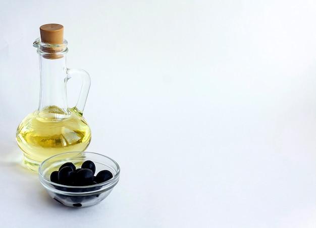 Óleo vegetal em uma garrafa de vidro e azeitonas pretas em uma tigela de vidro isolado em um fundo branco, copie o espaço