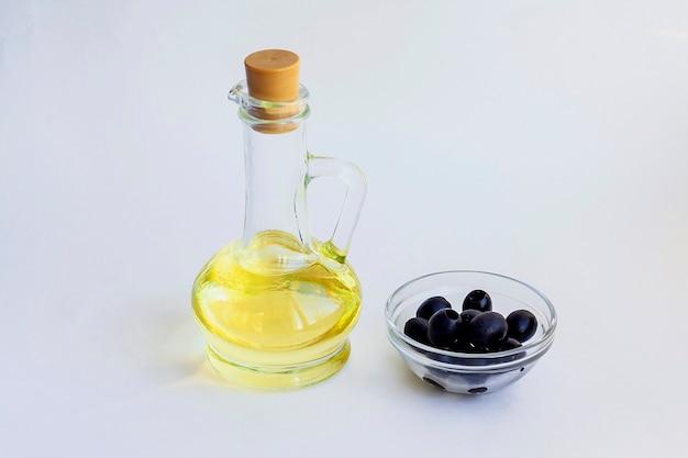 Óleo vegetal em uma garrafa de vidro e azeitonas pretas em uma tigela de vidro isolado em um fundo branco