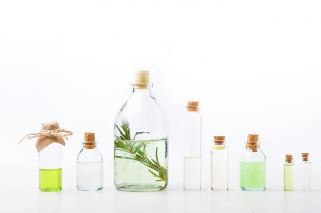 Óleos aromáticos nas garrafas de vidro em uma tabela branca. cuidados com o corpo. estilo de vida saudável. isolado.