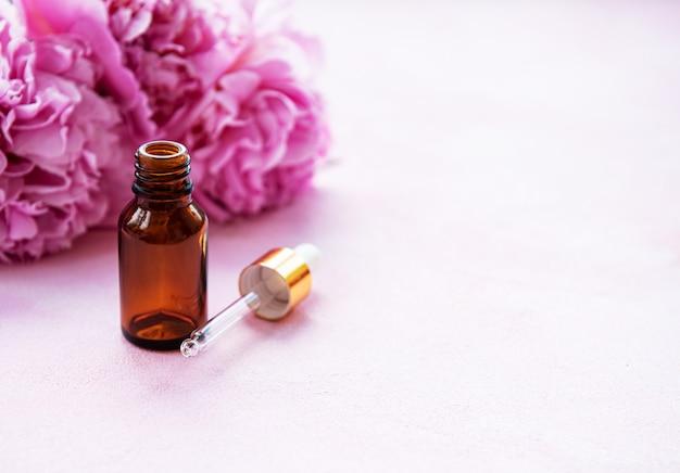 Óleos essenciais de aromaterapia e peônias cor de rosa