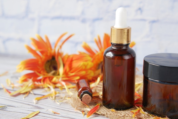 Óleos essenciais de eucalipto em frasco de vidro e flor na mesa