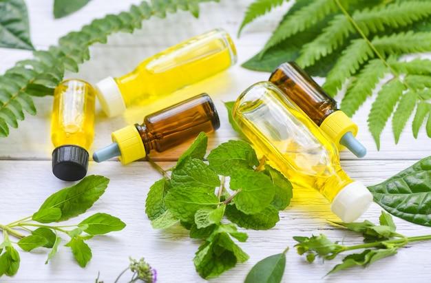 Óleos essenciais naturais em folhas de madeira e hortelã orgânicas