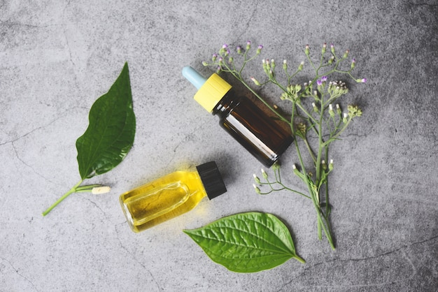 Óleos essenciais naturais em folhas de madeira e verdes orgânicos - aromaterapia frascos de óleo de ervas aroma com formulações de ervas de folhas, incluindo flores silvestres e ervas na vista superior de madeira