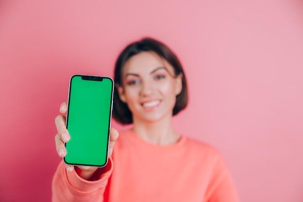 Olha esse celular! mulher feliz satisfeita aponta com o dedo indicador para a tela em branco, mostra o dispositivo moderno, emoções surpresas felizes.