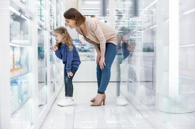 Olha mãe. mulher pensativa e positiva e menina em pé olhando para a vitrine