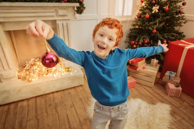 Olha o que eu tenho. alegre menino ruivo mantendo a boca bem aberta enquanto fica animado e posa com uma bola decorativa na mão.