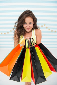 Olha o que eu tenho. menina compras de sexta-feira negra. garota feliz segurar sacolas de compras. anúncio de venda de sexta-feira negra. viciado em compras louco segura sacos de papel. escolha do cliente. eu amo tanto isso.