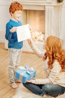 Olha o que tenho aqui. menino animado, olhando para a mãe com entusiasmo, enquanto lhe mostrava uma nova obra-prima em uma manhã de natal.