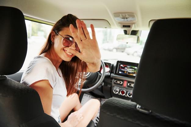 Olha para trás. mulher bonita no carro verde moderno. testando novo automóvel.