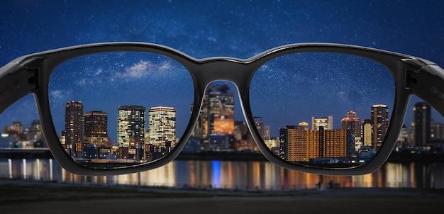Olhando a cidade à noite com o céu estrelado através de óculos