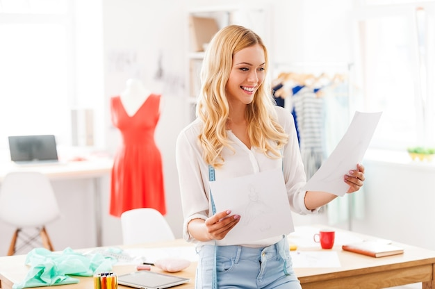 Olhando alguns designs. jovem alegre segurando papéis com desenhos e sorrindo enquanto se inclina para a mesa na oficina de moda