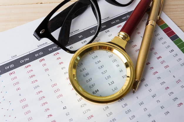 Olhando através de lupa para relatório financeiro