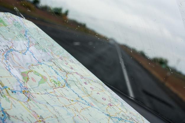 Olhando através de um pára-brisa com um mapa de estrada no painel