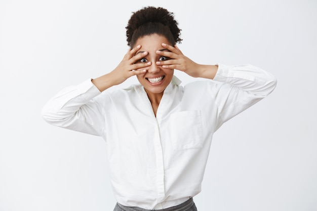 Olhando bem para você. retrato de uma encantadora mulher de negócios despreocupada e ativa com pele escura em uma camisa branca de escritório, cobrindo os olhos com as palmas das mãos e espiando por entre os dedos, fazendo careta, sorrindo