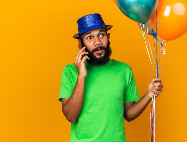 Olhando de lado, jovem afro-americano com chapéu de festa segurando balões falando no telefone isolado na parede laranja