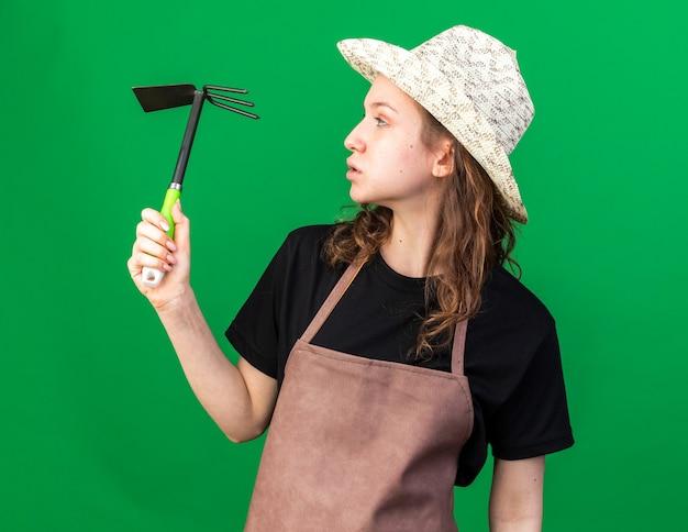 Olhando de lado, jovem jardineira com chapéu de jardinagem segurando um ancinho