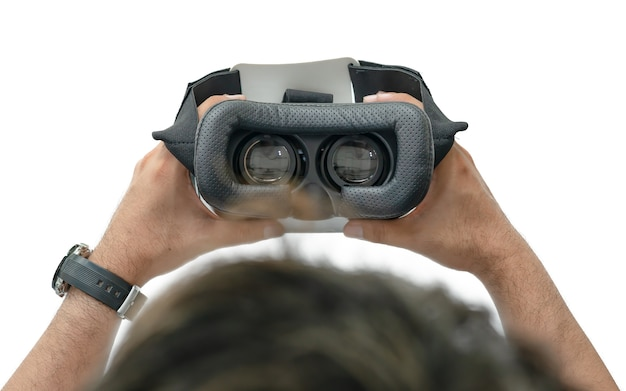 Olhando dentro de um auricular do vr ou do ar isolado no branco. mão segurando óculos vr.