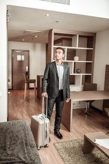 Olhando em volta. jovem empresário próspero de cabelos escuros olhando ao redor do quarto do hotel
