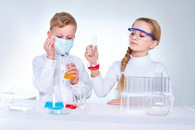 Olhando frasco estudante séria com o líquido químico