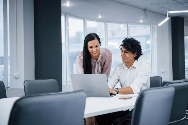 Olhando juntos para o computador. colegas de trabalho alegres em um escritório moderno, sorrindo ao fazer seu trabalho usando laptop