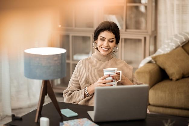 Olhando na tela. pacífica e atraente senhora passando um tempo em casa e assistindo a vídeos em um laptop cinza