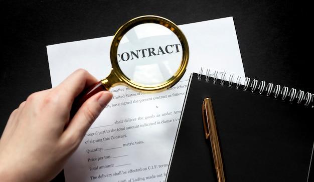 Olhando o contrato através da lupa em fundo preto
