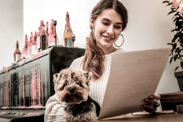 Olhando o menu. a mulher com um cachorro nas mãos lendo atentamente o menu