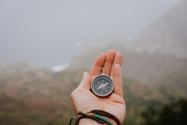 Olhando para a bússola para descobrir a direção certa. vale nebuloso e montanhas. santo antão. cabo verde